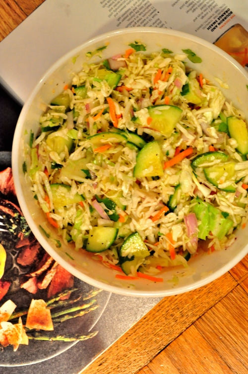 A bowl of zucchini coleslaw, featuring shredded cabbage, shredded carrots, zucchini chunks and more.