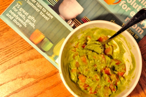 A bowl of simple guacamole featuring mashed, smooth avocado and chopped tomatoes