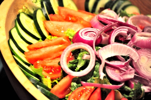 Salad bowl filled with sliced cucumbers, tomatoes, and red onion.