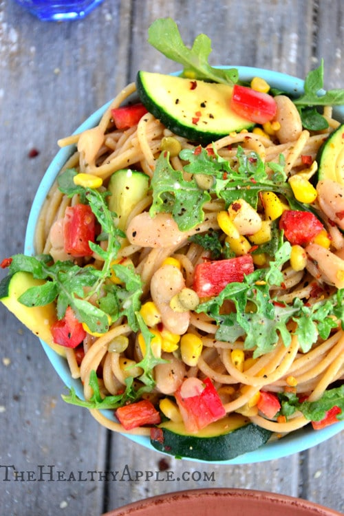 A bowl of pasta topped with corn, white beans, zucchini, arugula, and bright pops of red pepper.