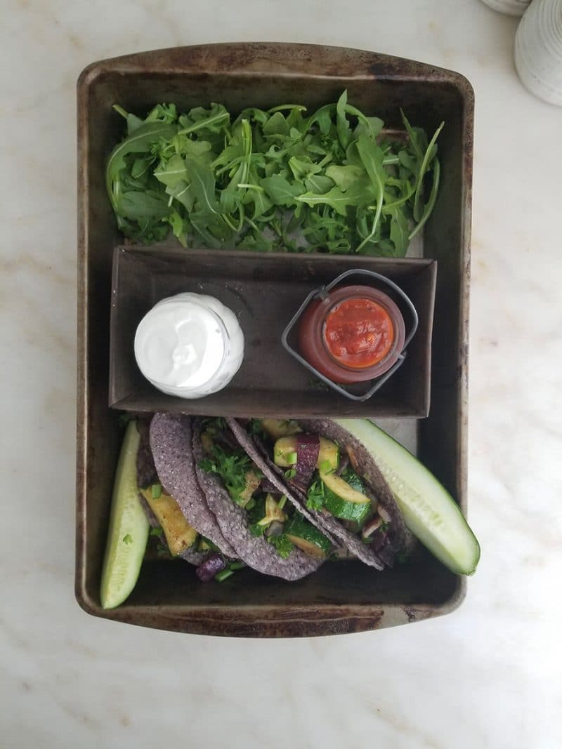 A spread of clean-eating tacos, dips, pickles, and arugula in a baking tray.