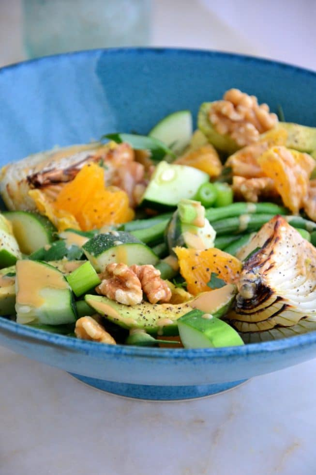 This French Green Bean Salad is ideal for lunch filled with avocado, oranges, walnuts, roasted onions and more in a deep blue bowl.