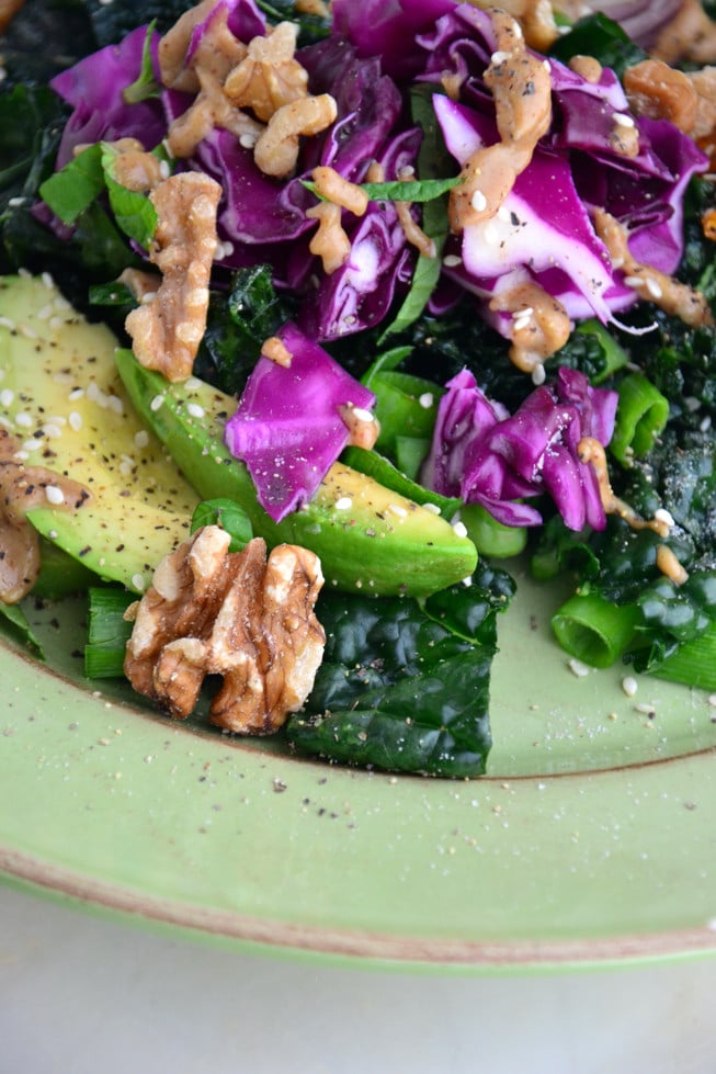 Kale avocado salad with a dairy-free creamy almond dressing on a green plate served for lunch.