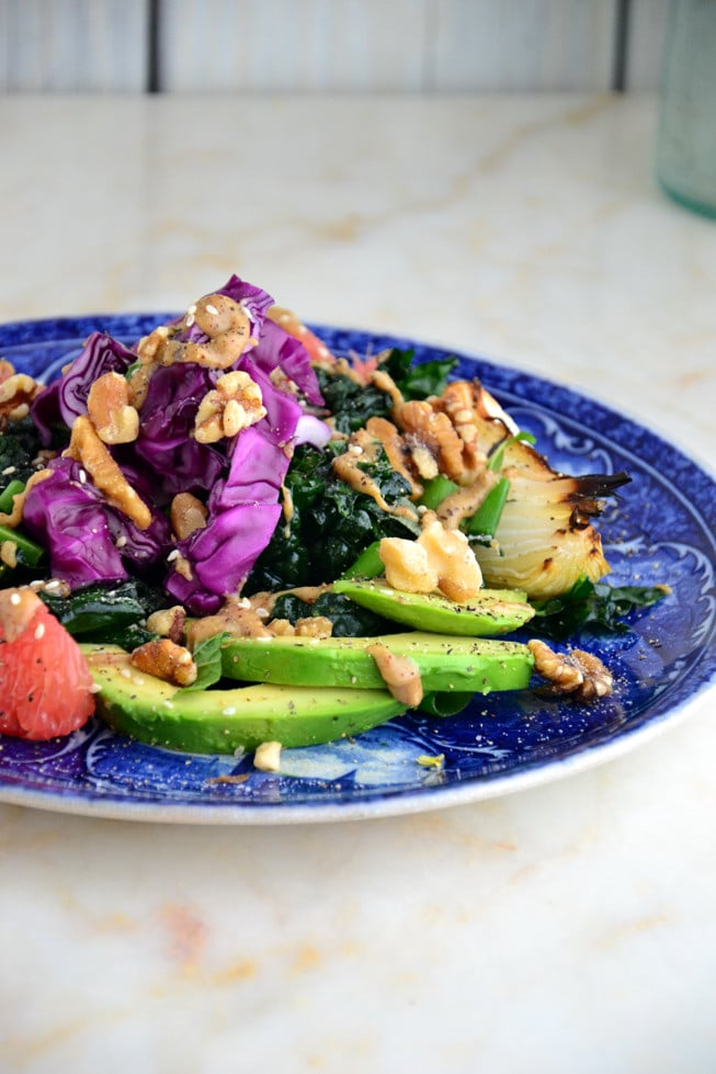 Easy massaged kale salad on a blue plate with avocado, grapefruit and walnuts.