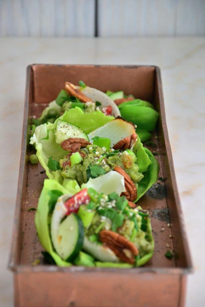 Vegetarian Lettuce Wraps on a gorgeous copper platter filled with guacamole, scallions, cucumbers and red bell peppers!