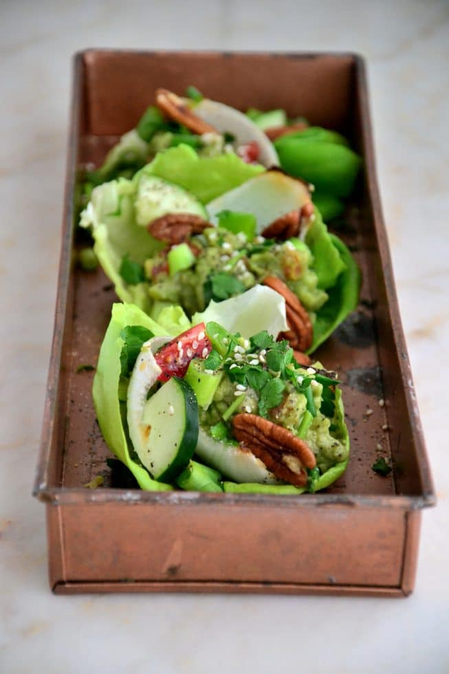 Vegetarian Lettuce Wraps filled with fresh veggies and guacamole on a beautiful copper platter.