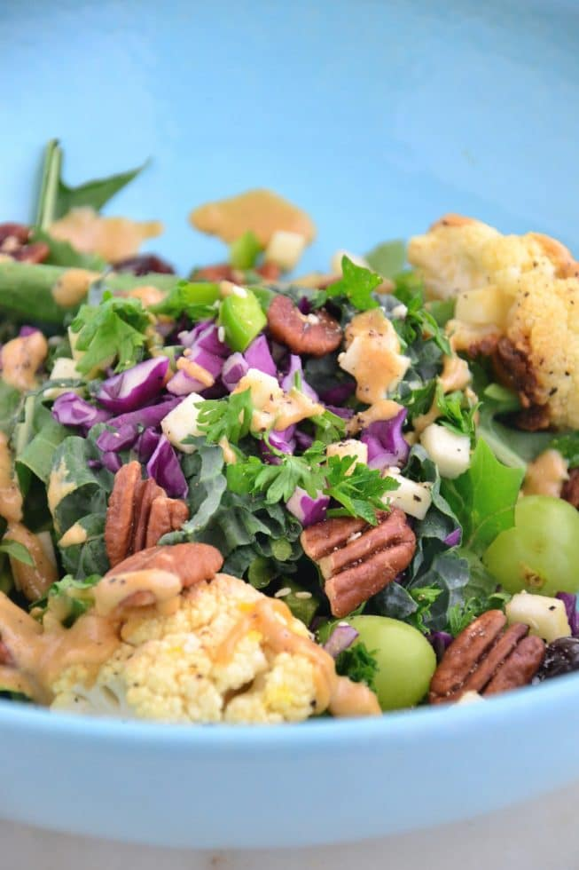 A delicious kale salad with roasted cauliflower, kale, pecans, green grapes and parsley in a light blue beautiful bowl.