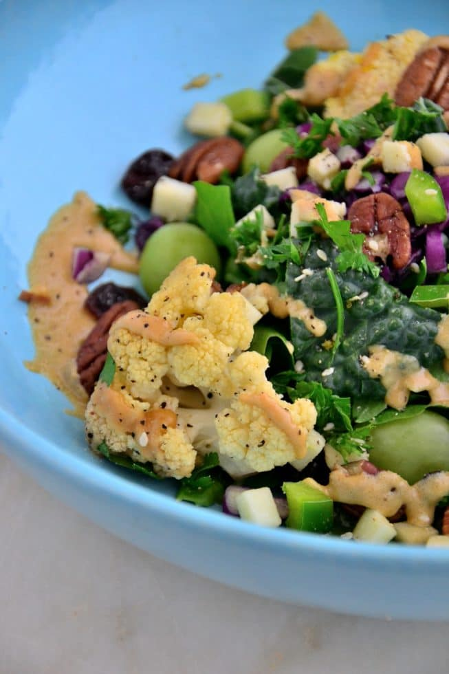 Gorgeous fresh green salad with roasted cauliflower, kale, pecans, green grapes and parsley in a light blue beautiful bowl.