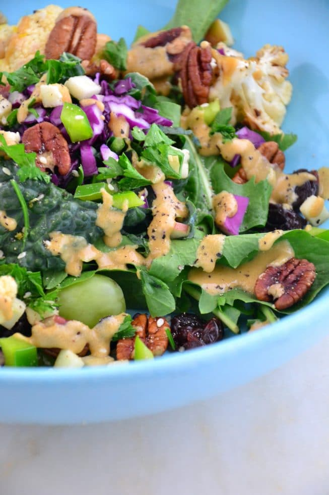 A beautiful blue bowl on a marble table top filled with kale salad and tahini dressing.