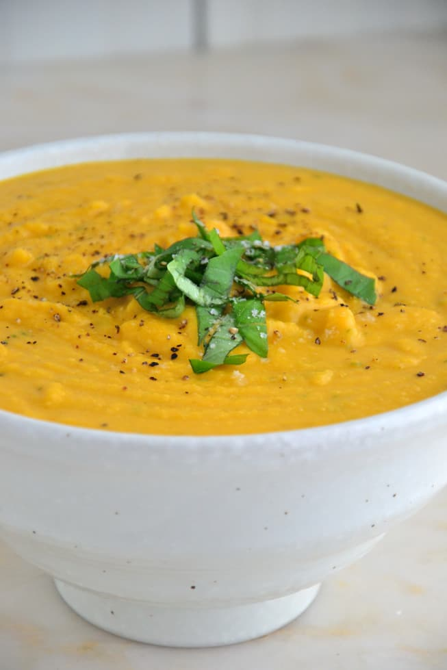 The best butternut squash soup with fresh basil poured into a lovely white bowl on a marble table.