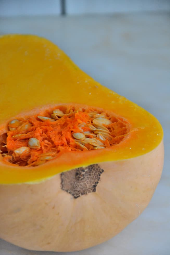 The best butternut squash soup involves slicing a butternut squash in half lengthwise.