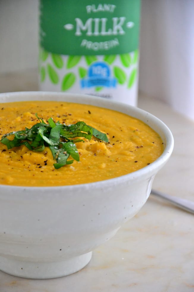 The best butternut squash soup is vegan and dairy-free and made with pea milk in a white bowl on a marble table.