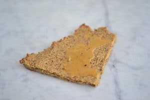 A slice of Paleo Pizza Crust with a drizzle of almond butter.