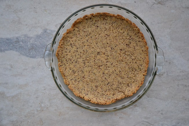 Gluten-free oatmeal pie crust right out of the oven and golden brown in a glass pie dish.