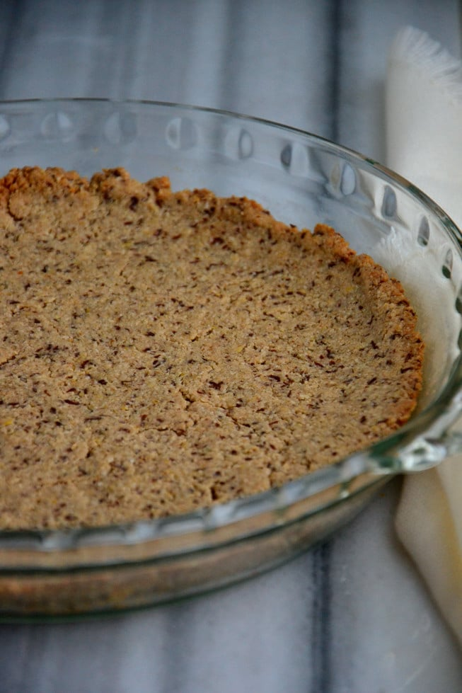 Pie crust made from oats, flax seeds and unsweetened coconut flakes in a glass pie dish after it's baked in the oven.