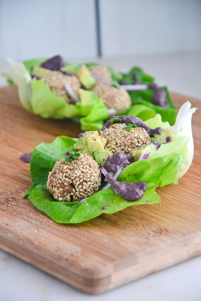 Gluten-Free Falafel in a large lettuce leaf with a cherry tahini vegan falafel dressing on a wooden serving board.