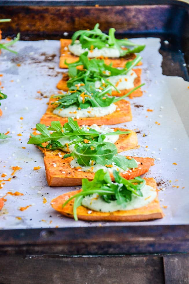 Roasted Sweet Potato Appetizer with dairy-free cream and arugula on top on a baking sheet.