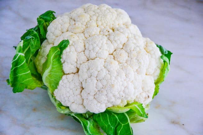 Whole head of cauliflower before it's roasted in the oven on a marble table.