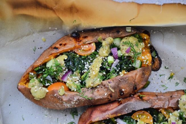 Healthy Oven Roasted Sweet Potatoes topped with veggies and an avocado sauce in a baking dish.