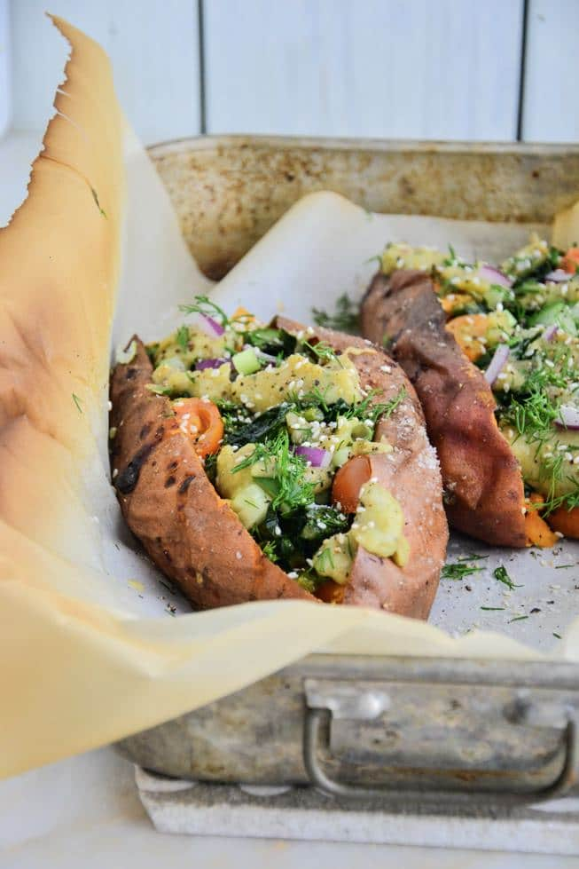 Healthy Oven Roasted Sweet Potatoes stuffed with vegetables and a creamy sauce in a baking dish with parchment paper.