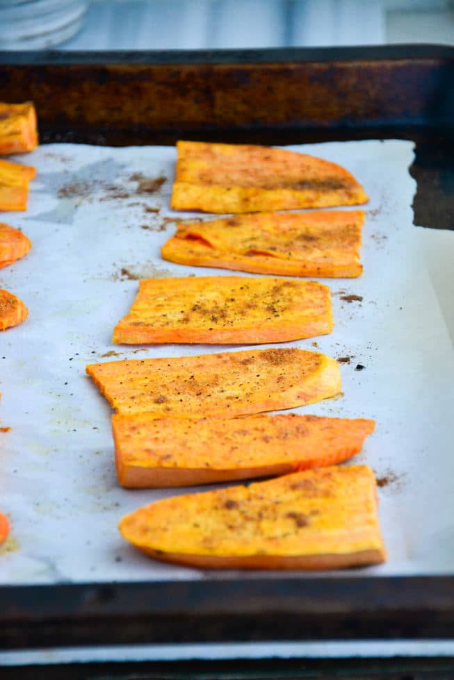 Roasted sweet potato appetizer on a baking sheet with parchment paper out of the oven.