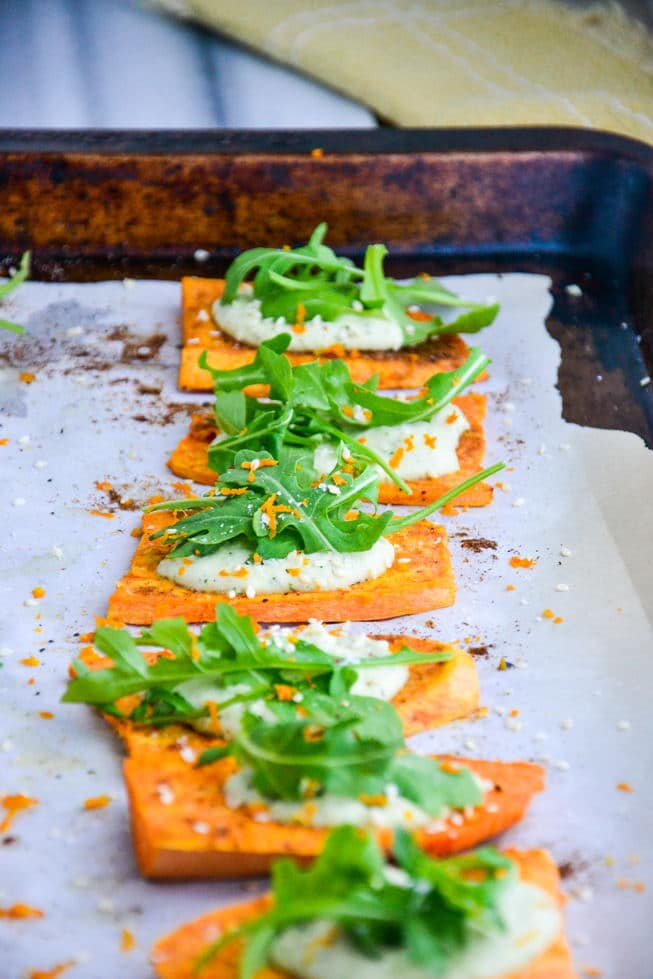 Sweet Potato Appetizer Bites on parchment paper on a baking sheet out of the oven.