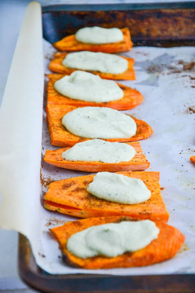 Roasted sweet potato appetizer with a dairy-free creamy sauce dolloped on top on a baking sheet with parchment paper.