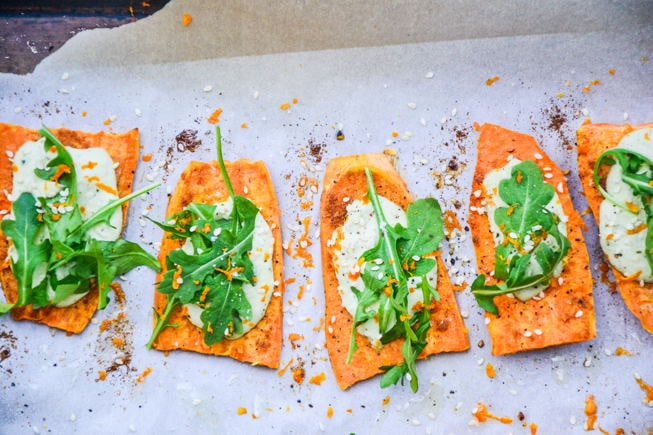 Sweet Potato Appetizer Bites overhead image with sea salt and pepper and fresh arugula on top.