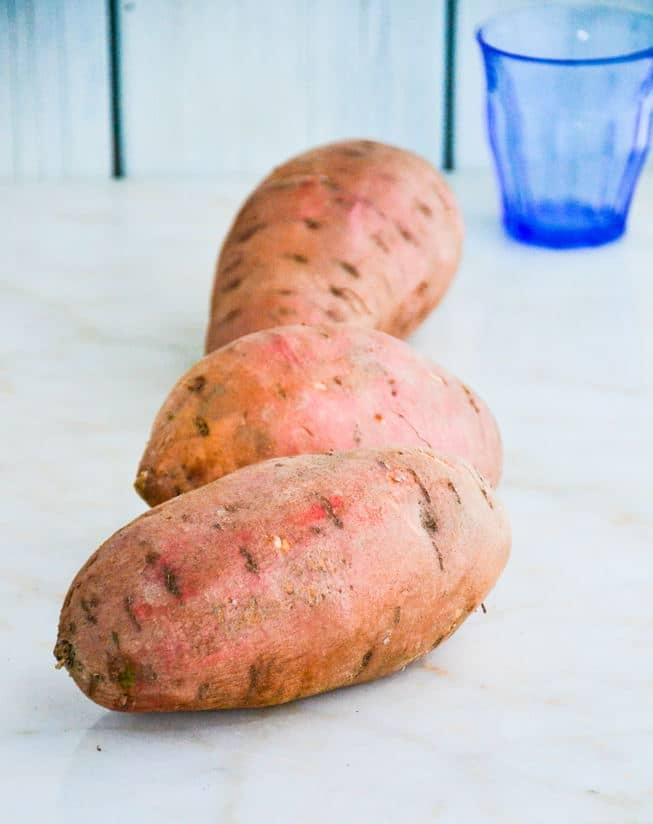 Three sweet potatoes on a marble table ready to be roasted in the oven.