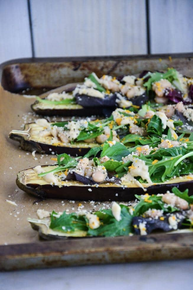 Roasted eggplant with arugula on top and hemp seeds on a baking sheet.