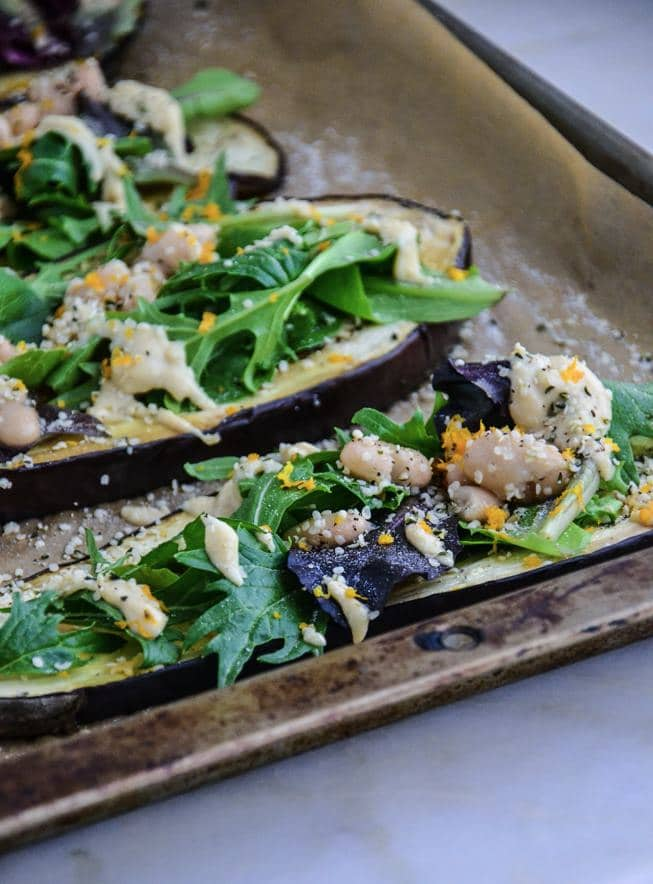 Roasted eggplant appetizer with a white bean sauce on top on a baking sheet ready to eat.