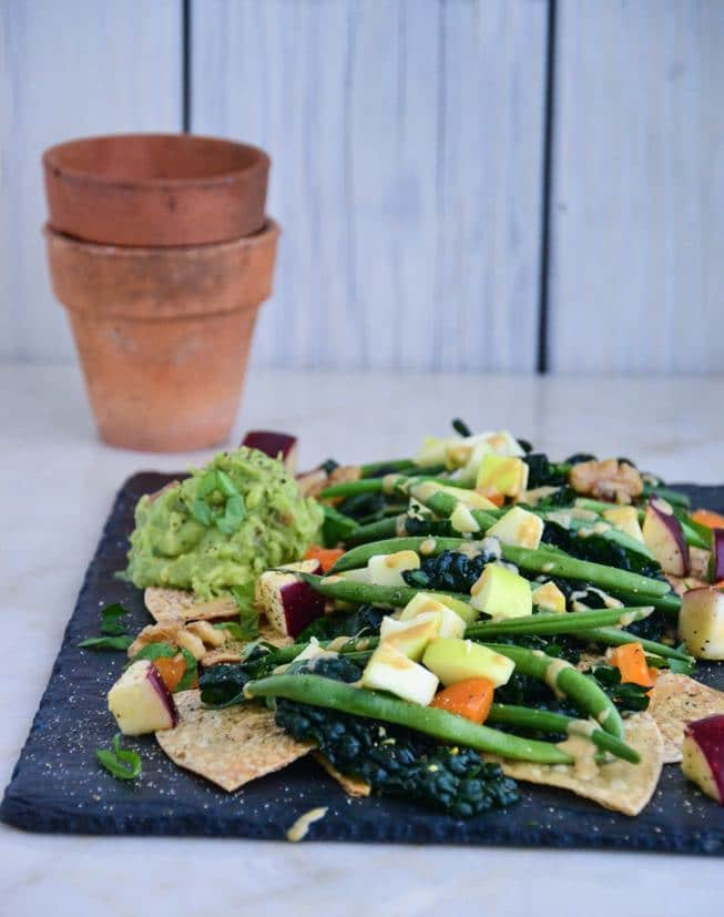 The best veggie nachos filled with kale and other veggies and homemade tortilla chips on a slate and a marble table with fruit and guacamole, too.