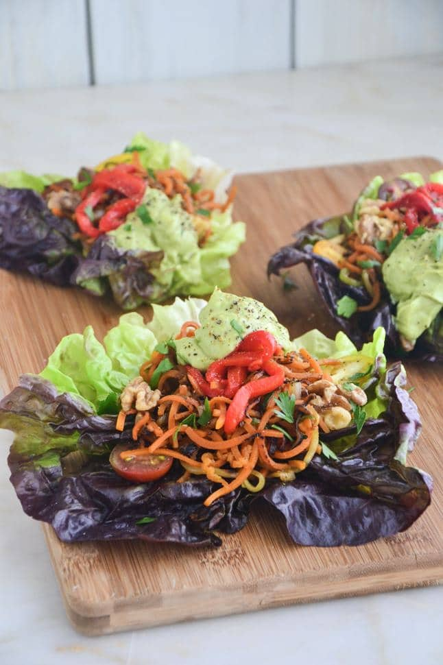 Fajita Lettuce Wraps with avocado sauce on a large cutting board with veggies on a marble tabletop.