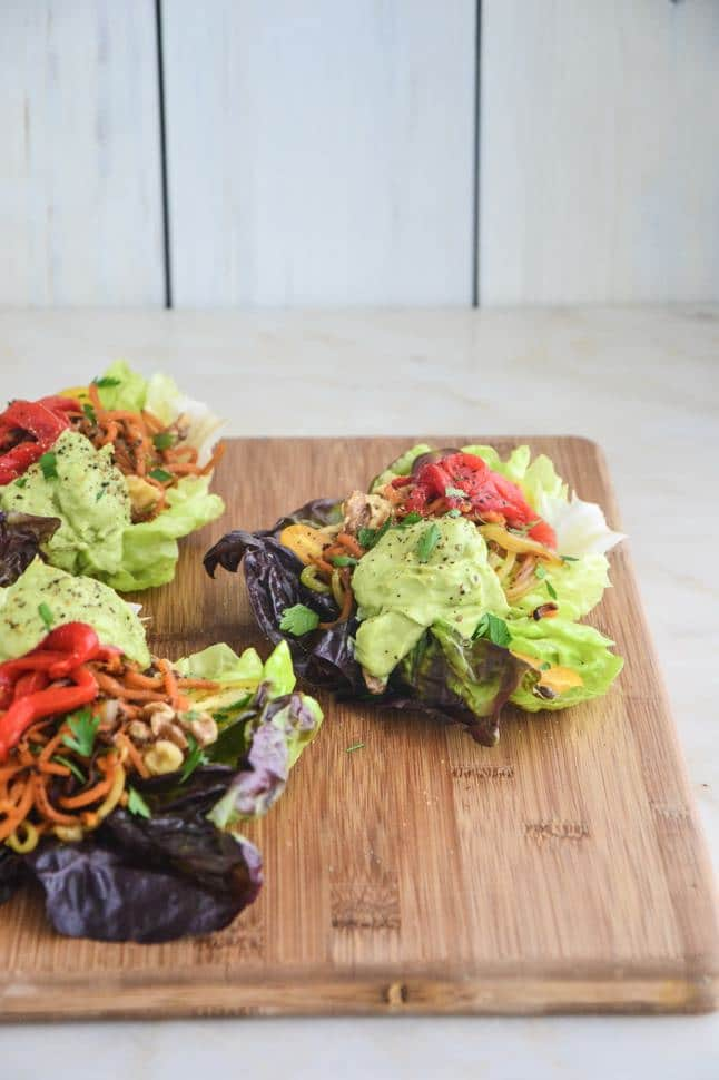 Fajita Lettuce Wraps with avocado sauce on a large cutting board with veggies.