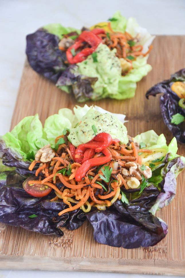 Fajita Lettuce Wraps with zucchini and carrots on a cutting board.