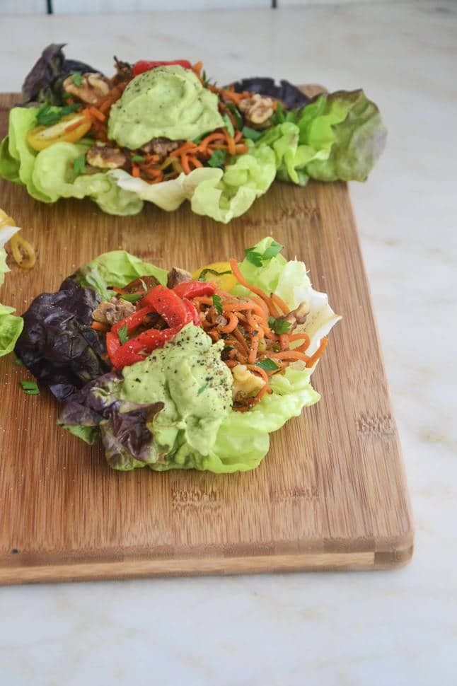 Fajita Lettuce Wraps with avocado sauce on a wooden cutting board with veggies.