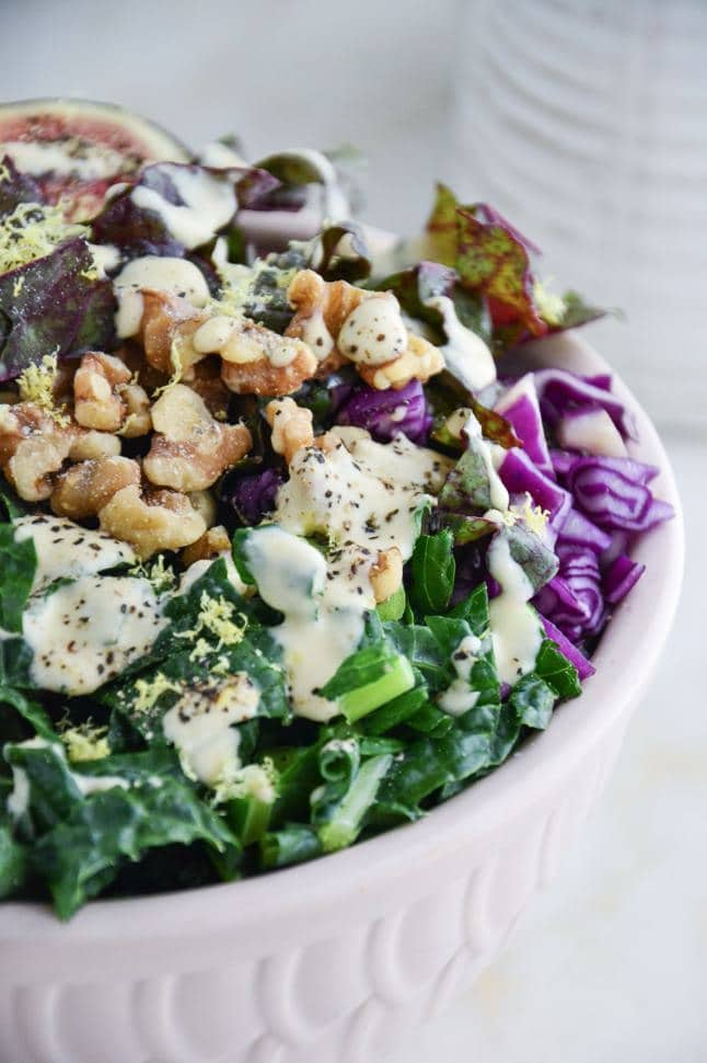 Dinosaur kale salad with tahini dressing, walnuts, fresh figs and purple cabbage in a pink bowl on clean marble table.