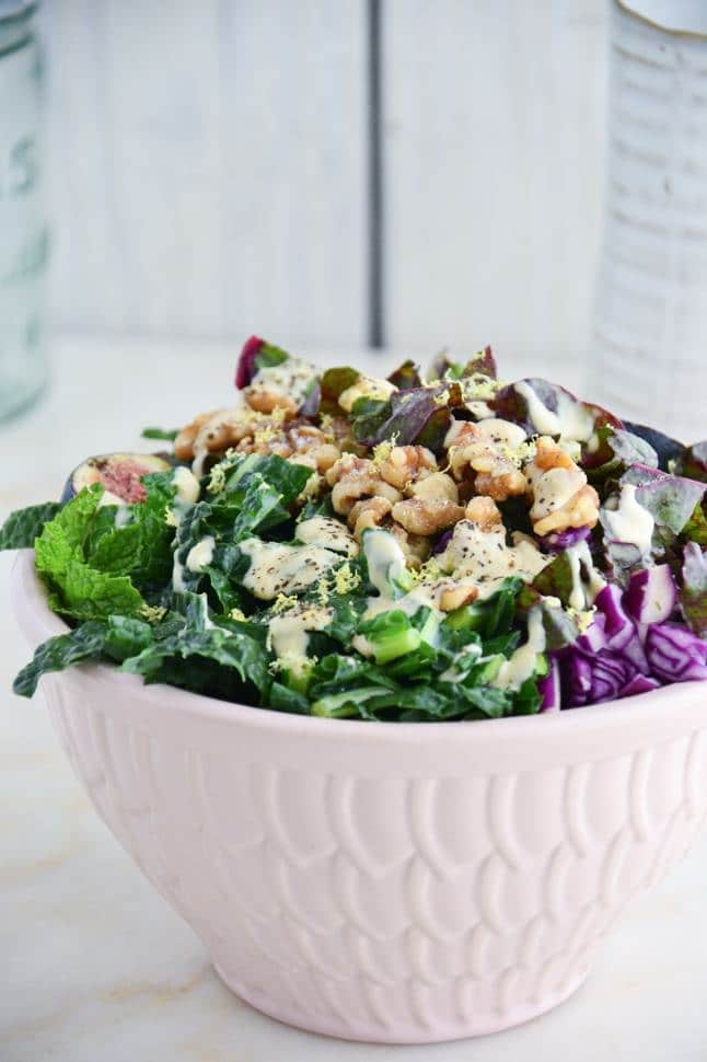 Dinosaur kale salad with tahini dressing, walnuts, figs and red cabbage in a pink bowl on marble table.