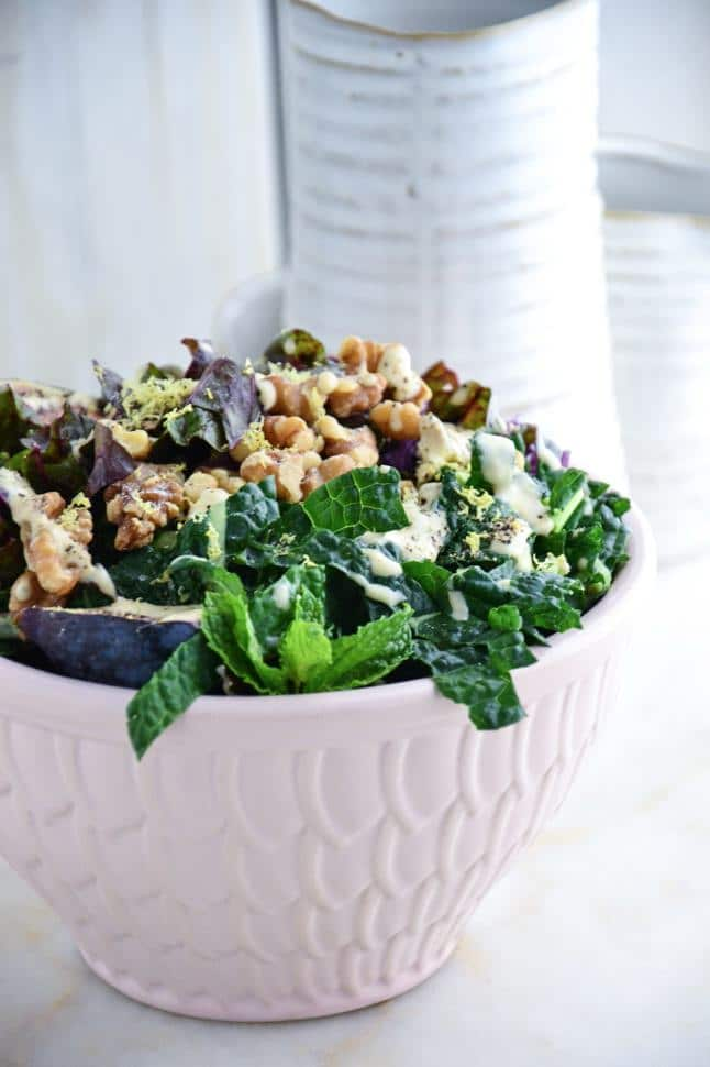 Dinosaur kale salad with tahini dressing, walnuts, fresh figs and purple cabbage, fresh mint and Swiss chard in a pink bowl on clean marble table.