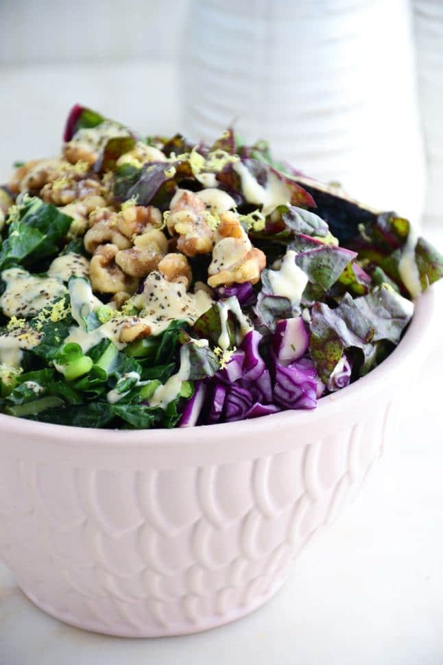 Delicious kale salad with tahini dressing, walnuts, figs and red cabbage in a pink bowl on marble.