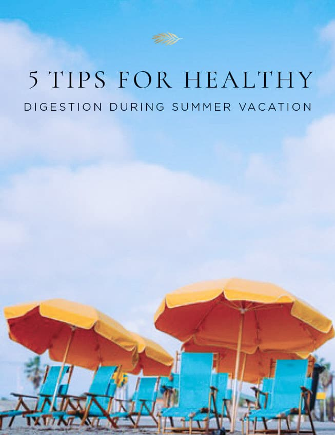 5 tips for healthy digestion on vacation on a beach with sand and blue skies and orange umbrellas and blue beach chairs.