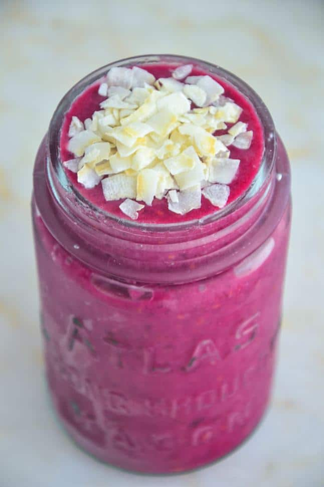 Red velvet beet smoothie in a glass jar on a marble table top.