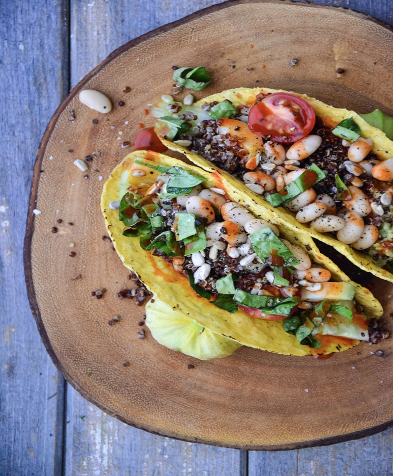 White Bean tacos on a wooden platter on a marble table with tomatoes.