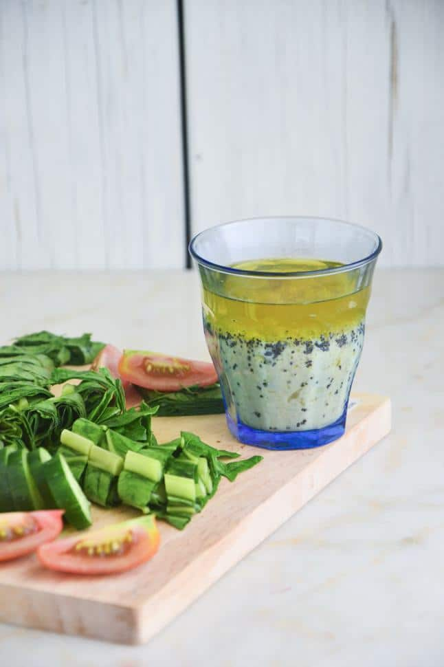 Lemon poppy seed dressing in a cup on a cutting board with chopped fresh veggies.