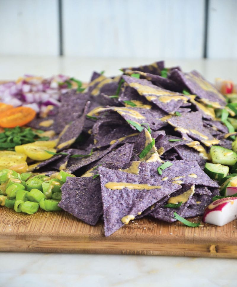 Blue gluten-free chips with tahini sauce and toppings on a wooden cutting board.