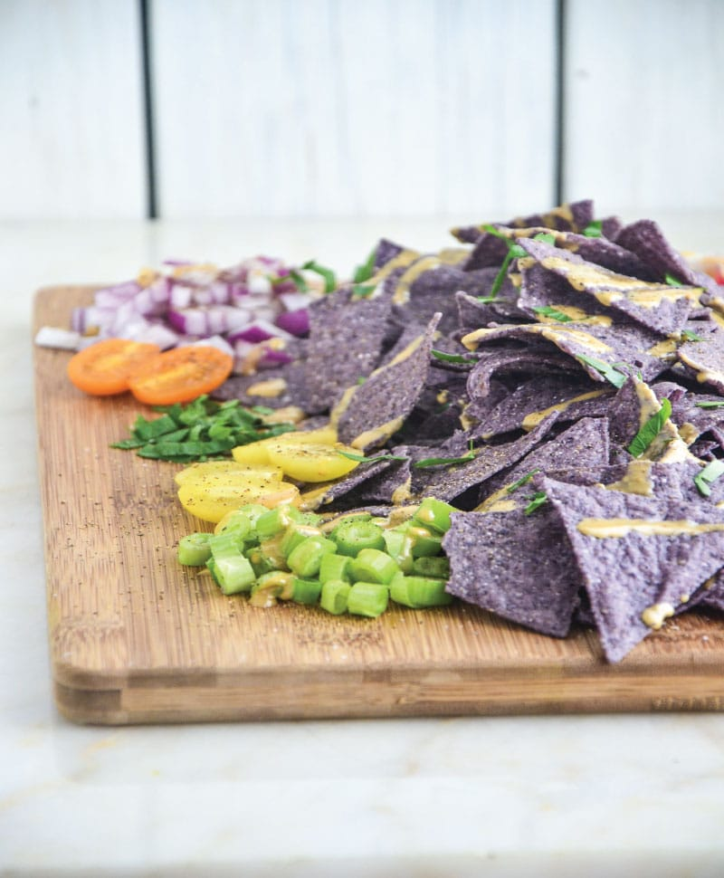 Blue whole-grain tortilla chips piled on a wooden cutting board with scallions, tomatoes, cucumber, and onion.