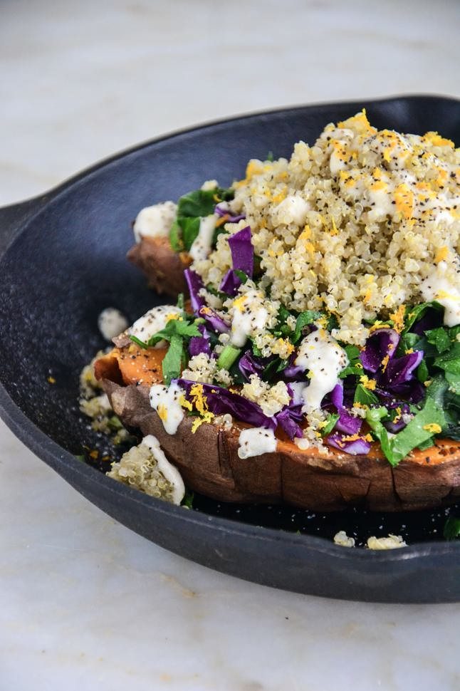 A sweet potato piled high with quinoa, purple cabbage, and greens on a cast iron skillet.