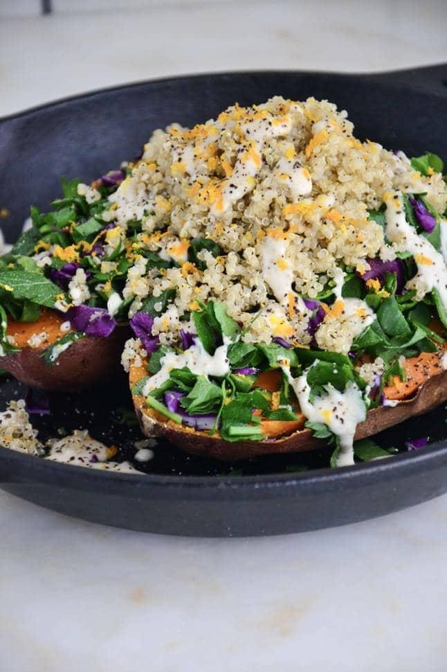 A vegetarian stuffed sweet potato, filled with quinoa and veggies, spilling over into a skillet.