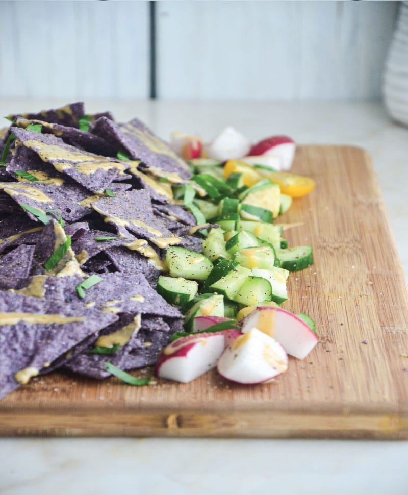 Delicious corn chips drizzled with garlic tahini sauce and topped with veggies.