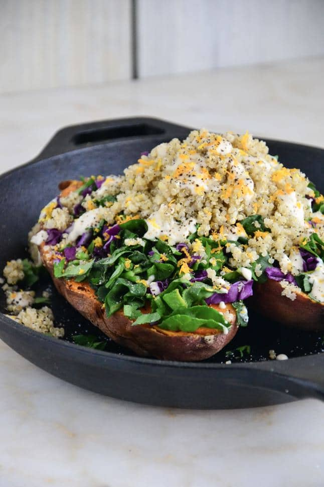 A sweet potato split in half and packed with veggies and quinoa, topped with orange zest.